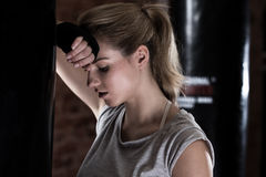 Tired girl next to punch bag Royalty Free Stock Photography