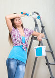 Tired girl painting walls Royalty Free Stock Images