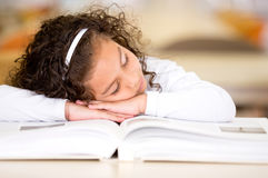 Tired girl reading a book Stock Images