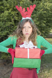 Tired girl with reindeer ears holding Christmas presents Royalty Free Stock Photo