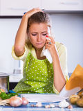 Tired girl signing financial papers at kitchen Stock Photo