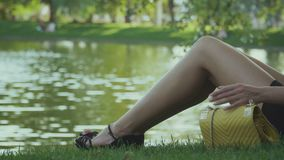 Tired girl sits near the pond and relax on green grass stock video footage
