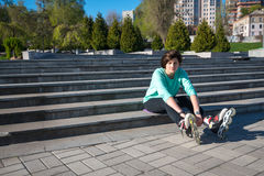 Tired girl sits on the steps in the park, stretching out her leg. S and arms, relaxing after roller skating and looking at the camera. Wonderful morning in the Royalty Free Stock Photography