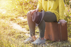 Tired girl sitting and resting on brown vintage suitcase in the field road during summer sunset. Toned image and travel concept. Royalty Free Stock Photos