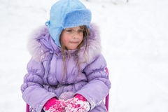 Tired girl sitting on a sled Stock Photos