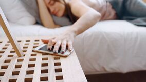 Tired girl sleep in cozy bed with orthopedic mattress chic bright apartment, phone with set alarm clock lies on wooden