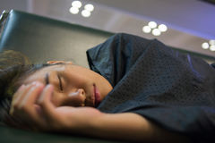 Tired girl sleeping in the airport because flight delay. Tired girl sleeping in the airport because the flight delay Royalty Free Stock Photos