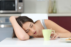 Tired girl sleeping at breakfast. Tired girl sleeping on the table of the kitchen at breakfast Royalty Free Stock Photography