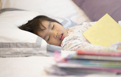 Tired girl sleeping heavy duties Reading Stock Photos