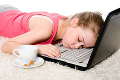 Tired girl sleeping on the laptop. Stock Photo