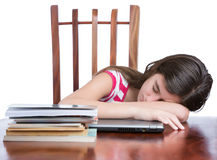 Tired girl sleeping over her laptop with a stack of books on the table. Tired female teen student sleeping over her laptop with a stack of books on the table Stock Photos