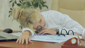 Tired girl sleeping resting her head on the table stock footage