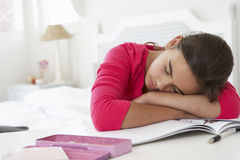 Tired Girl Sleeping Whilst Doing Homework At Desk In Bedroom Royalty Free Stock Photography