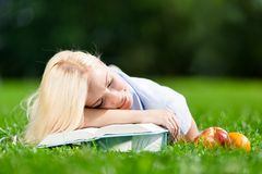Tired girl sleeps on the books lying on the grass Stock Photography