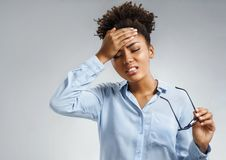 Tired girl suffering from painful headache and stress. Photo of african american woman in blue shirt holding hand on forehead on gray background. Medical stock photography