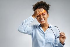 Tired girl suffering from painful headache and stress. Photo of african american woman in blue shirt holding hand on forehead on gray background. Medical stock photos