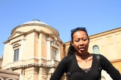 Tired girl in Vatican Museum. Tired Indonesian girl - young woman in black clothes and sunglasses standing in front of building of Vatican Museum in Vatican city Royalty Free Stock Photos