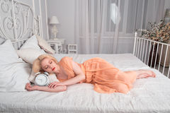 Tired girl wants to sleep and sets the alarm. Royalty Free Stock Images