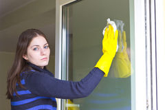 Tired girl washing windows at home Royalty Free Stock Image