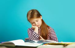 Tired girl in weary state reads book at her desk and experiences dissatisfaction. Lazy student does not want to learn. Concept of education and training royalty free stock images