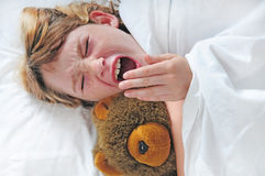 Tired girl yawning in bed Stock Photo