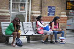 Tired Girls who collected money for charity, is sitting on a bench near the train station Liverpool station Royalty Free Stock Photos