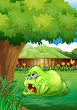 A tired green monster near the tree Royalty Free Stock Images
