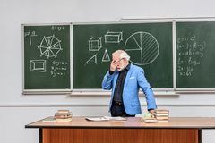 Tired grey hair professor touching eyes. At blackboard stock photos