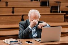 Tired grey hair professor touching nose. Bridge royalty free stock photos