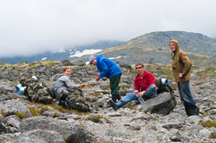 Tired group of backpackers in mountains Stock Images