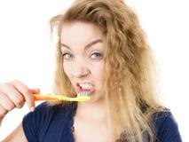 Grumpy tired woman brushing teeth, isolated Stock Photography