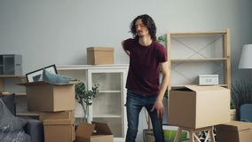 Tired guy bringing heavy boxes in room suffering from backache during relocation. Tired guy is bringing heavy boxes in room suffering from backache touching back stock footage