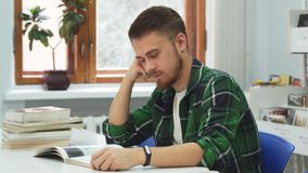 Tired guy falls asleep while studying. A young man is sitting over a book. He begins to fall asleep and immediately wakes up. Young guy is sitting in the stock footage