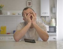 Tired young guy sitting on the background of the kitchen stock photo