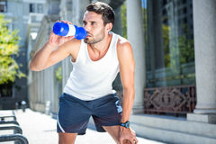 Tired handsome athletic drinking out of bottle Royalty Free Stock Photos