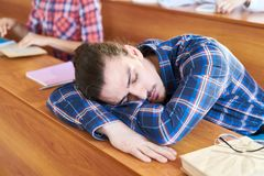 Tired student sleeping on desk royalty free stock photography