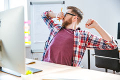 Tired handsome man stretching and yawning on workplace Stock Photos