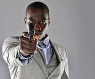 Man in a suit aims his firearm at the viewer Stock Photography