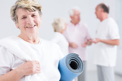 Tired but happy after fitness session at senior club. Portrait of a very optimistic elderly women at the gym, holding her towel and exercise mat Stock Image