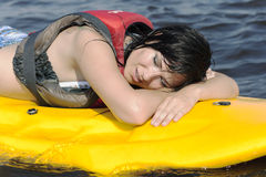 Tired but happy girl after training lies on surfin Royalty Free Stock Images