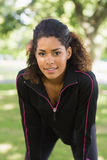 Tired healthy woman taking a break while jogging in park Stock Photos