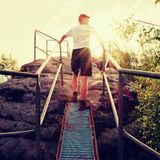 Tired hiker keep handrail on peak. Sunny spring daybreak in rocky mountains. Hiker with red baseball cap, dark pants and white shi Stock Photo
