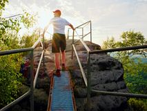 Tired hiker keep handrail on peak. Sunny spring daybreak in rocky mountains. Hiker with red baseball cap, dark pants and white shi Royalty Free Stock Image