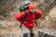 Tired hiker man hiking in mountains dressed in red clothes exploring new places. Traveler bearded male trekking and mountaineering. During his journey. Travel royalty free stock photo
