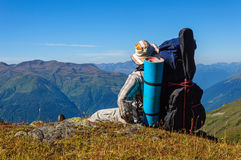 Tired hiker relaxes on a slope in the mountains Stock Photography