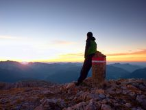 Tired hiker sit on border stone on Alps mountain. Austria Germany border. Daybreak above foggy valley Stock Images