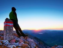 Tired hiker sit on border stone on Alps mountain. Austria Germany border. Daybreak above foggy valley Stock Photography