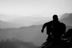 Tired hiker with sporty backpack sit on rocky peak and watching into deep misty valley bellow. Sunny spring daybreak in rocky moun Stock Photography