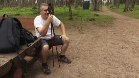 Tired hiker with walking sticks resting in park on bench stock video footage