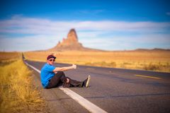 Tired hitch-hiker sitting on a road Stock Images